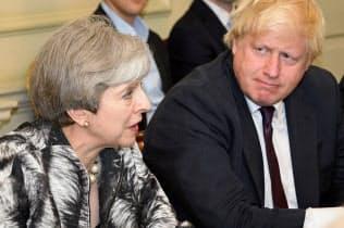 辞めるメイ英首相(左)の後任候補に挙がるジョンソン前外相=ロイター