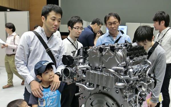 新型エンジンの模型に見入る来場者ら(1日、広島県府中町)