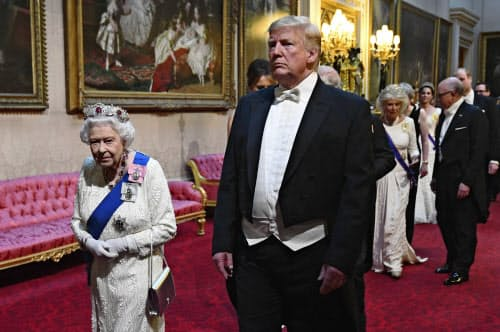 晩さん会会場へ移動するエリザベス女王(左)とトランプ米大統領(3日、ロンドンのバッキンガム宮殿)=AP