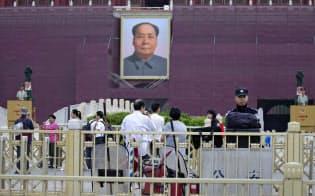 4日、天安門の毛沢東肖像の前で警戒する警察官ら=AP