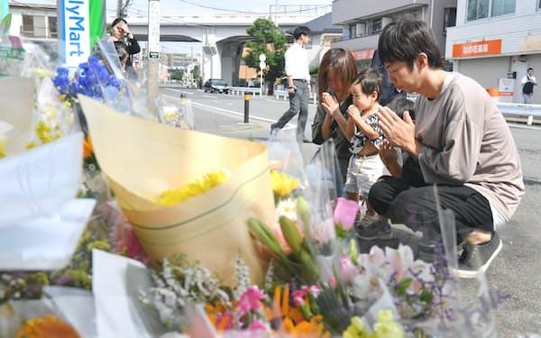 事件から一週間がたち、多くの花が供えられた現場付近で手を合わせる家族連れ(4日午前、川崎市多摩区)