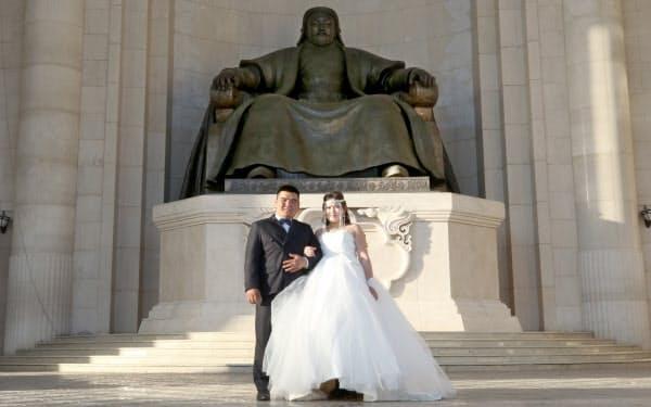 チンギスハン像の前で記念写真に納まる新郎新婦