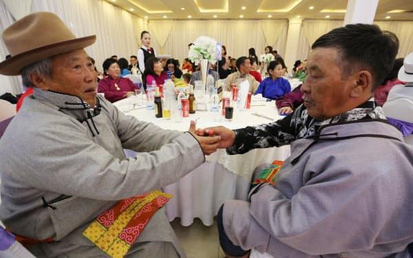 披露宴会場の円卓で、伝統的なあいさつの「嗅ぎたばこ」交換をする出席者