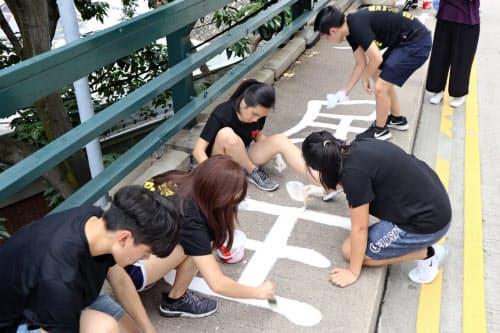 香港大学で天安門事件に絡むメッセージを塗り直す学生たち(4日、香港)
