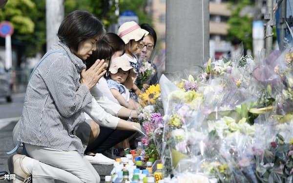 児童らが殺傷された事件から1週間、川崎市多摩区の現場で手を合わせる人たち(4日午後)=共同