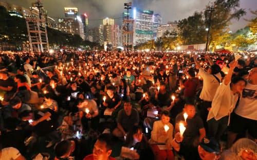 追悼集会でろうそくをともす人たち(4日、香港)=三村幸作撮影