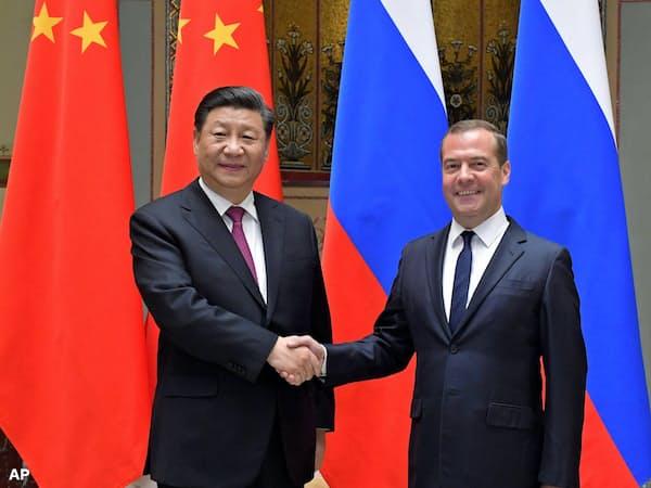 6日、モスクワで会談前に握手する中国の習近平国家主席とロシアのメドベージェフ首相=AP