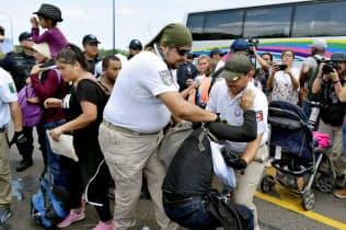 不法移民を拘束する移民当局の職員(5日、チアパス州)=ロイター