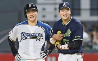 適時打を放ち、ヤクルトの一塁手村上(右)と笑顔で話す日本ハム・清宮。2年目の若手が存在感を見せた3連戦だった=共同