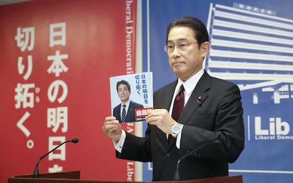 参院選の公約を手に記者会見に臨む自民党の岸田政調会長(7日、党本部)