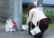 池田詩梨ちゃんが衰弱死した事件で現場のマンション前に献花をする人(7日午後、札幌市)=共同