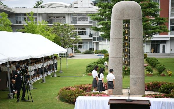 「祈りと誓いの塔」の鐘を鳴らし、黙とうする児童(8日午前、大阪府池田市の大阪教育大付属池田小)