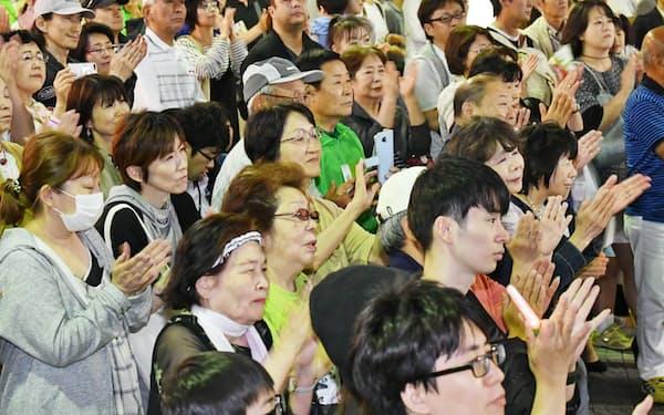 街頭で候補者の最後の訴えを聞く有権者ら(8日、堺市)