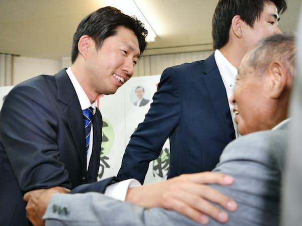 堺市長選で当選を決め、支援者にあいさつする大阪維新の会の永藤英機氏(左)(9日午後、堺市)
