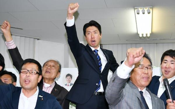 堺市長選で当選を決め、気勢を上げる大阪維新の会の永藤英機氏(中央)=9日午後、堺市