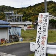 高知県四万十町に置かれた地震や津波への備えを呼び掛ける看板。奥は津波避難タワー=共同