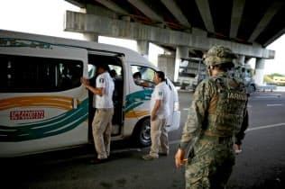 道路を警備する軍警察官(9日、メキシコ南部チアパス州)=ロイター