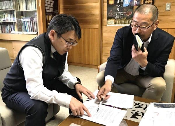 ふるさと納税の対象外となった説明を受ける和歌山県高野町の平野町長(左)(5月14日)