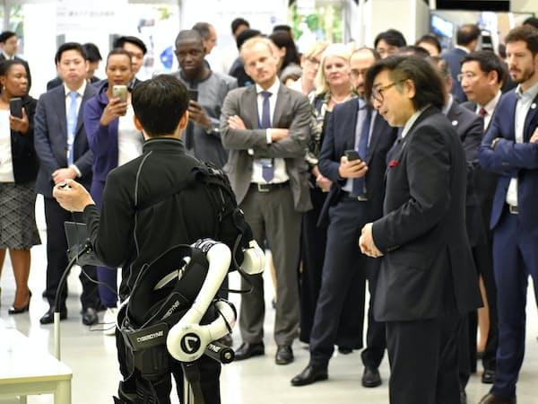 装着型ロボット「HAL」を各国の閣僚らに説明する山海社長(手前右、9日、茨城県つくば市)