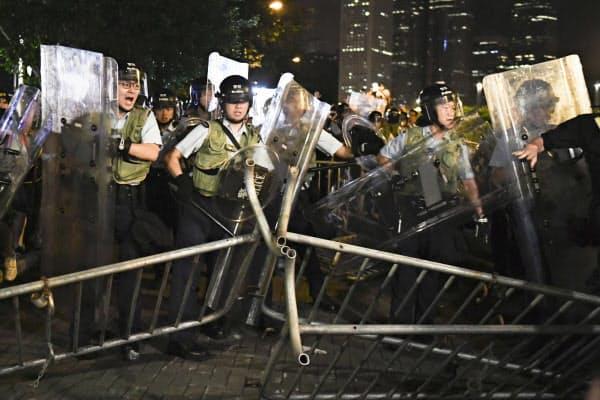 「逃亡犯条例」改正案の反対デモ終了後、若者らが設置したフェンスを倒す警官隊(10日、香港)=共同