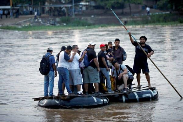 いかだでグアテマラからメキシコへ渡る中米移民(10日、メキシコ南東部チアパス州)=ロイター