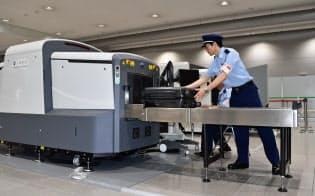 税関職員が新型X線検査装置にトランクを通す