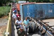 封鎖が解除された橋を通り、コロンビアへ向かうベネズエラ人ら(ベネズエラ西部タチラ州)=ロイター