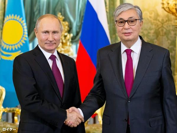 ナザルバエフ氏の辞任に伴いカザフスタン大統領に昇格したトカエフ氏(右)と握手するロシアのプーチン大統領(4月、モスクワ)=ロイター