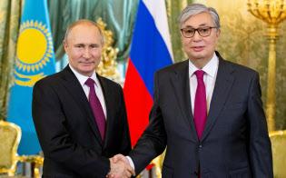 ナザルバエフ氏?#26410;?#20219;に伴いカザフスタン大統領に昇格したトカエフ氏(右)?#20219;?#25163;するロシアのプーチン大統領(4月、モスクワ)=ロイター