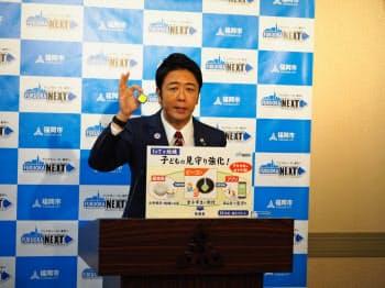 見守りサービスで使うビーコン端末を持つ高島市長(10日、福岡市)