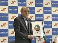 アルベルギ・ディフージ・ジャパン協会のロゴマークを掲げる岡山商議所の松田会頭(10日、岡山市)