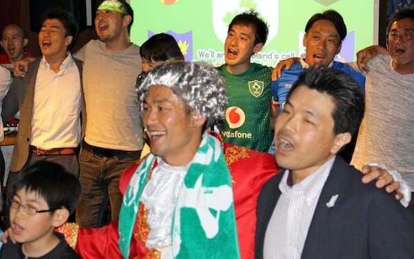 広瀬俊朗さん(前列中央)と肩を組んで国歌を合唱するラグビーファン(横浜市都筑区)