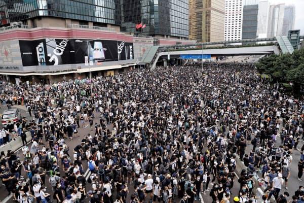 道路を占拠して抗議する人たち(12日、香港)=ロイター