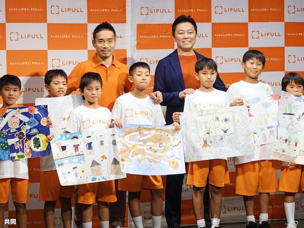 東京都内で開かれたイベントで、子どもたちと記念撮影に応じるサッカー日本代表の長友=奥左(12日)=共同