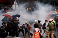 催涙ガスに反応するデモ隊(12日、香港)=ロイター