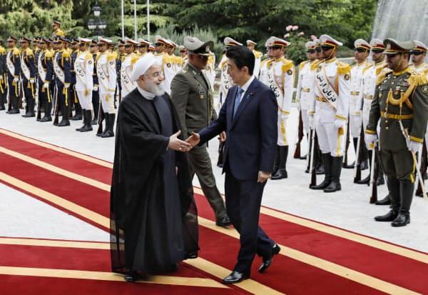 歓迎式典でイランのロウハニ大統領(左)と握手する安倍首相(12日、テヘラン)=共同