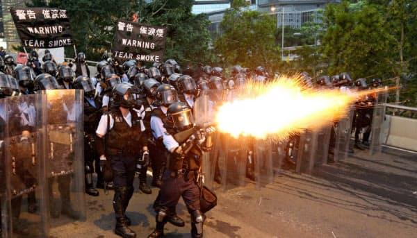 デモ隊に催涙弾を発射する警察官(12日、香港)=ロイター