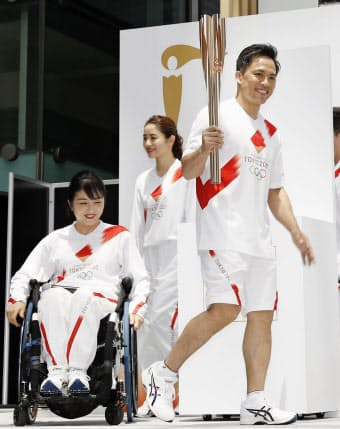 20年東京五輪聖火リレーのルート概要などを発表するイベントで、トーチを手に聖火ランナーのユニホームを着て登場した公式アンバサダーの野村忠宏さん(右)ら=共同