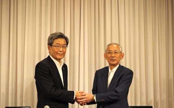 会長職の交代を終え、握手する北海道経済連合会の真弓明彦新会長(左)と高橋賢友前会長(13日、札幌市)