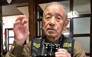 インパール作戦の体験談を語る佐藤哲雄さん。手にしているのは従軍時に携行した双眼鏡(新潟県村上市)