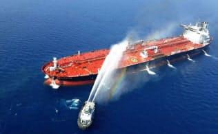イラン海軍の艦艇が、攻撃されたタンカーの消火作業に当たっている=ロイター