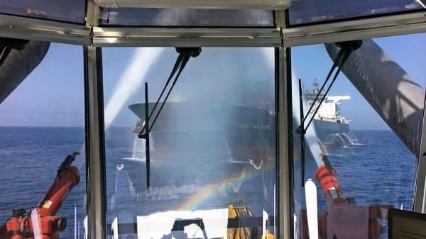 火災が起き、消火活動の放水を受ける台湾中油のタンカー(13日、オマーン湾)=Frontline提供・AP