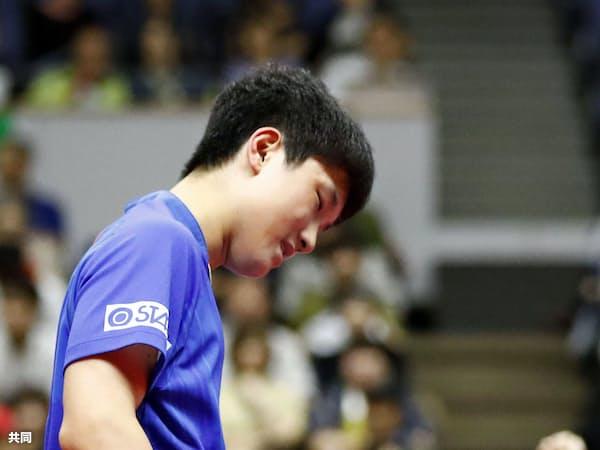 男子シングルス1回戦で孫聞(奥)にポイントを奪われ、肩を落とす張本智和(14日、北海きたえーる)=共同