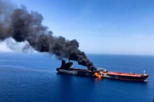 ホルムズ海峡近くで13日、攻撃を受け、炎上するタンカー=ロイター