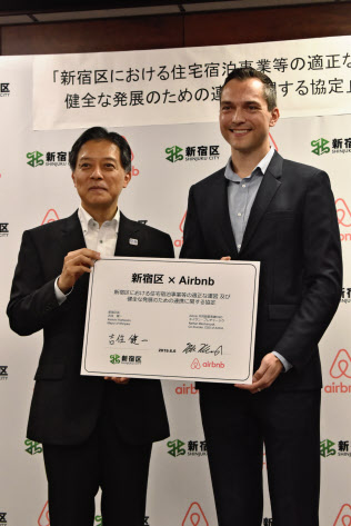 米民泊大手と連携協定を結んだ東京都新宿区の吉住健一区長(写真左)