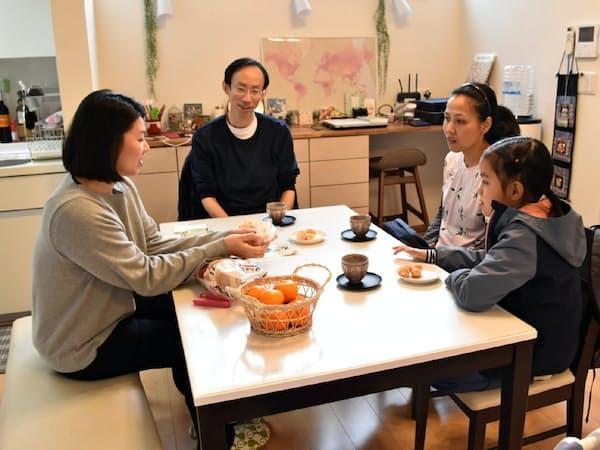 戸建て型の民泊施設で住人の日本人女性(左)と交流するタイ人一家