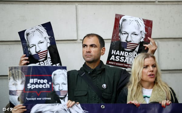 英治安裁判所前でアサンジ被告の米国への身柄引き渡しに反対する人々(14日、ロンドン)=ロイター