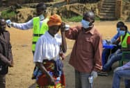 コンゴの国境付近で体温のチェックを受ける人たち=AP
