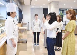フィールドワークで学内のカフェの店長にインタビューする学生(京都市左京区)