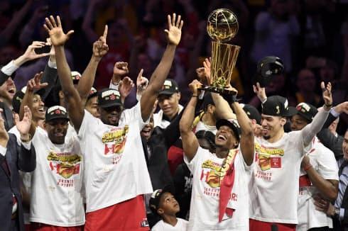 カナダ勢で初めてNBAの頂点に立ち、優勝トロフィーを掲げて喜ぶラプターズの選手ら=AP